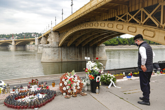 A man stands by candles and flowers placed near the Margit Bridge over the Danube river during a memorial ceremony for the victims, one year after the Mermaid boat accident, in Budapest, Hungary, Friday, May 29, 2020. Commemorations are taking place on the one year anniversary of the Danube River tragedy in which a sightseeing boat carrying mostly tourists from South Korea sank after a collision with a river cruise ship that killed at least 27 people. (AP Photo/Laszlo Balogh)