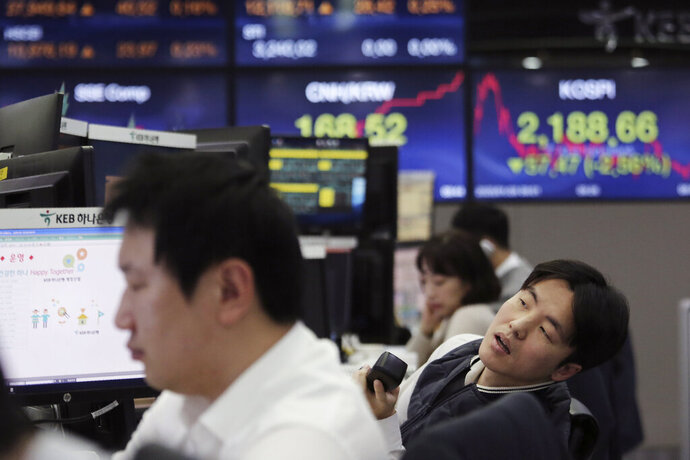 A currency trader watches monitors at the foreign exchange dealing room of the KEB Hana Bank headquarters in Seoul, South Korea, Tuesday, Jan. 28, 2020. Asian shares continued to fall Tuesday, dragged down by worries about an outbreak of a new virus in China that threatens global economic growth. (AP Photo/Ahn Young-joon)