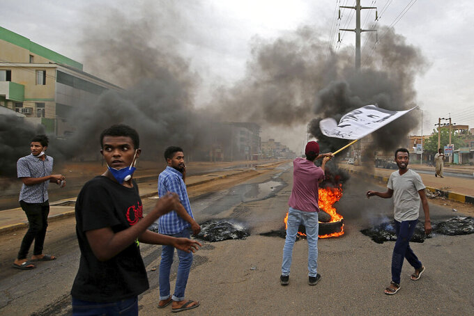Sudanese men burn tyres during a demonstration to commemorate the first anniversary of a deadly crackdown carried out by security forces on protesters during a sit-in outside the army headquarters, in Khartoum, Sudan, Saturday, May 23, 2020. (AP Photo/ Marwan Ali)