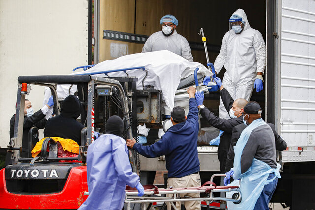 A body wrapped in plastic is unloaded from a refrigerated truck and handled by medical workers wearing personal protective equipment due to COVID-19 concerns, Tuesday, March 31, 2020, at Brooklyn Hospital Center in the Brooklyn borough of New York. The body was moved to a hearse to be removed to a mortuary. The new coronavirus causes mild or moderate symptoms for most people, but for some, especially older adults and people with existing health problems, it can cause more severe illness or death. (AP Photo/John Minchillo)