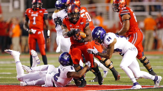 Utah running back Zack Moss, center, carries the ball as Weber State's Jawian Harrison Jr. (2) and Jordan Preator (24) defend during the second half of an NCAA college football game Thursday, Aug. 30, 2018, in Salt Lake City. (AP Photo/Rick Bowmer)