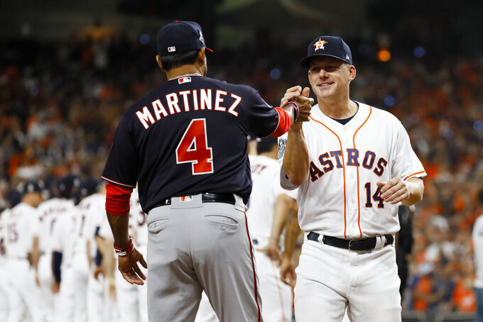 Houston Astros manager AJ Hinch, right, and Washington Nationals manager Dave Martinez meet during introductions before Game 1 of the baseball World Series Tuesday, Oct. 22, 2019, in Houston. (AP Photo/Matt Slocum)