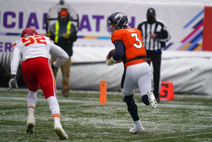 Denver Broncos quarterback Drew Lock runs en route to scoring a touchdown as Kansas City Chiefs defensive end Tanoh Kpassagnon defends during the first half of an NFL football game Sunday, Oct. 25, 2020, in Denver. (AP Photo/Jack Dempsey)