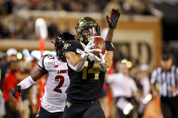 Wake Forest wide receiver Sage Surratt, front, scores on a 47-yard reception against Louisville during the second half of an NCAA college football game in Winston-Salem, N.C., Saturday, Oct. 12, 2019. Louisville won 62-59. (AP Photo/Nell Redmond)