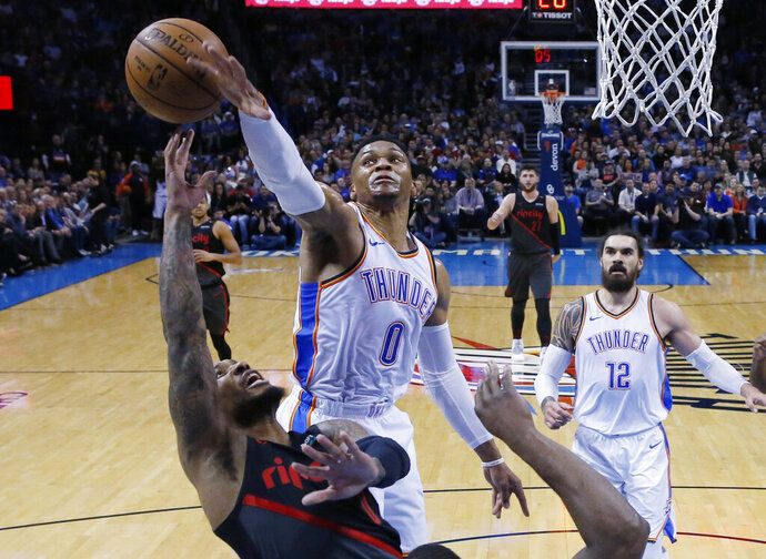 Oklahoma City Thunder guard Russell Westbrook (0) blocks a shot by Portland Trail Blazers guard Damian Lillard, left, in the first half of an NBA basketball game in Oklahoma City, Monday, Feb. 11, 2019. (AP Photo/Sue Ogrocki)