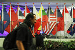 A journalist walks past ASEAN member country flags at the Suntec Convention Centre during the 33rd ASEAN summit in Singapore, Monday, Nov. 12, 2018. (AP Photo/Yong Teck Lim)