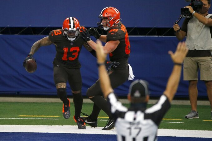 Back judge Steve Patrick (17) signals as Cleveland Browns' Odell Beckham Jr. (13) and Harrison Bryant (88) celebrate Beckham's touchdown late in the second half of an NFL football game against the Dallas Cowboys in Arlington, Texas, Sunday, Oct. 4, 2020. (AP Photo/Michael Ainsworth)
