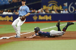 Minnesota Twins' Josh Donaldson slides into third on a wild pitch in front of Tampa Bay Rays third baseman Joey Wendle during the third inning of a baseball game on Sunday, Sept. 5, 2021, in St. Petersburg, Fla. (AP Photo/Scott Audette)
