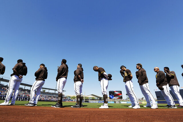 San Diego Padres players and coaches line up during playing of the national anthem before a spring training baseball game against the Los Angeles Dodgers, Monday, March 9, 2020, in Peoria, Ariz. (AP Photo/Elaine Thompson)