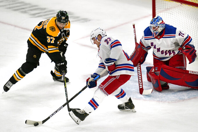 New York Rangers defenseman Adam Fox (23) clears the puck away from Boston Bruins center Patrice Bergeron (37) during the first period of an NHL hockey game, Saturday, May 8, 2021, in Boston. At right is New York Rangers goaltender Keith Kinkaid. (AP Photo/Charles Krupa)