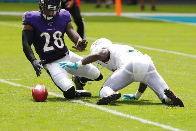 Miami Dolphins wide receiver Jakeem Grant (19) drops a punt return as Baltimore Ravens defensive back Justin Bethel (28) attempts to grab it, during the first half at an NFL football game, Sunday, Sept. 8, 2019, in Miami Gardens, Fla. (AP Photo/Wilfredo Lee)