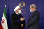 In this photo released by the official website of the office of the Iranian Presidency, President Hassan Rouhani, left, talks with his Minister of Health and Medical Education Saeed Namaki during a meeting in Tehran, Iran, Saturday, July 4, 2020. Iran on Sunday instituted mandatory mask-wearing as fears mount over newly spiking reported deaths from the coronavirus, even as its public increasingly shrugs off the danger of the COVID-19 illness it causes. (Iranian Presidency Office via AP)