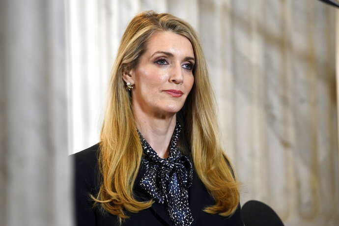 FILE - In this March 20, 2020, file photo, U.S. Sen. Kelly Loeffler, R-Georgia, waits to speak in a television interview on Capitol Hill in Washington. Candidates in the special election for the U.S. Senate seat held by Loeffler are set to square off in their first debate Monday, Oct. 19, 2020. Loeffler faces a large field including Democrat Raphael Warnock and fellow Republican Doug Collins in a race for the seat she was appointed to 10 months earlier. (AP Photo/Susan Walsh, File)