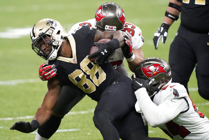New Orleans Saints running back Ty Montgomery (88) is hit by Tampa Bay Buccaneers defenders during the second half of an NFL divisional round playoff football game, Sunday, Jan. 17, 2021, in New Orleans. (AP Photo/Brynn Anderson)