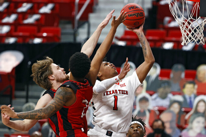 Texas Tech's Terrence Shannon Jr. (1) lays up around Incarnate Word's Marcus Larsson (15) and Keaston Willis (2) during the first half of an NCAA college basketball game Tuesday, Dec. 29, 2020, in Lubbock, Texas. (AP Photo/Brad Tollefson)