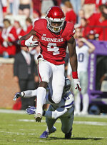 Oklahoma running back Trey Sermon (4) jumps away from a tackle by Kansas State defensive back Walter Neil Jr. (15) in the first of an NCAA college football game in Norman, Okla., Saturday, Oct. 27, 2018. (AP Photo/Sue Ogrocki)