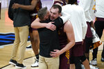 Loyola Chicago head coach Porter Moser celebrates with Cameron Krutwig (25) after beating Illinois 71-58 in a men's college basketball game in the second round of the NCAA tournament at Bankers Life Fieldhouse in Indianapolis, Sunday, March 21, 2021. (AP Photo/Paul Sancya)