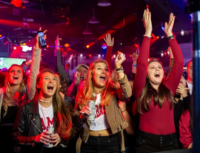 From front left to right, Meaghan Hourigan, Brigit Hourigan and Megan Richardson cheer the Crimson Tide along with other fans pulling for Alabama against Clemson as they watch a broadcast of an NCAA college football playoff championship game Monday, Jan. 7, 2019, at Rounders on the Strip in Tuscaloosa, Ala. (AP Photo/Vasha Hunt)