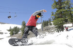 FILE - In this July 1, 2017 file photo, a snowboarder cuts throughout the snow at the Squaw Valley Ski Resort in Squaw Valley, Calif. A proposal to connect two Lake Tahoe ski resorts with a 2.2-mile-long (3.5-kilometer-long) gondola has moved closer to final approval. Placer County's approval of the project on Tuesday is one of the