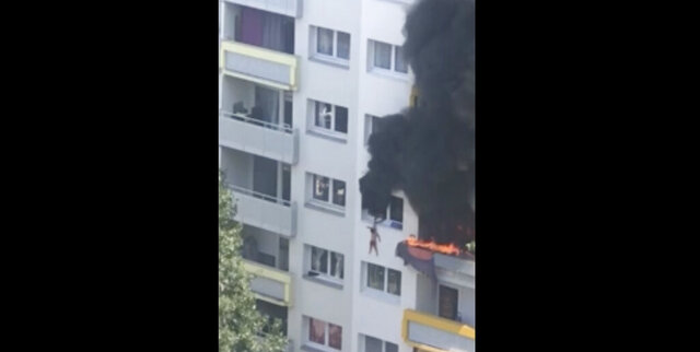 In this grab taken from video, a boy hangs from a window as flames engulfed an apartment as onlookers below prepare to catch him, in Grenoble, France, Tuesday, July 21, 2020. A boy and a toddler escaped a blaze at an apartment in the southeastern French city of Grenoble on Tuesday after they jumped into the arms of residents. The two brothers, aged three and 10 years old, were hanging from a window as flames engulfed their home and onlookers below screamed for them to jump down. (AP)