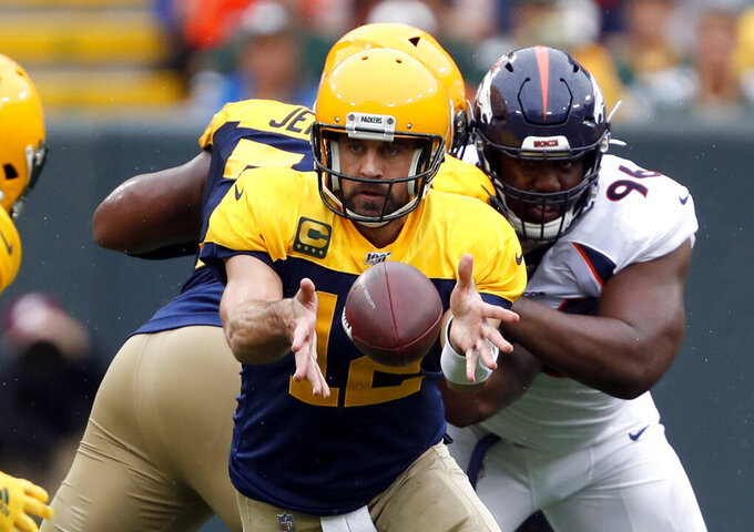 Green Bay Packers quarterback Aaron Rodgers pitches the ball to running back Aaron Jones during the first half of an NFL football game against the Denver Broncos Sunday, Sept. 22, 2019, in Green Bay, Wis. (AP Photo/Matt Ludtke)
