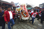 Nepalese devotees perform a traditional elephant dance during Indra Jatra festival, an eight-day festival that honors Indra, the Hindu god of rain, in Kathmandu, Nepal, Friday, Sept. 13, 2019. Families gather for feasts and at shrines to light incense for the dead, and men and boys in colorful masks and gowns representing Hindu deities dance to the beat of traditional music and devotees' drums, drawing tens of thousands of spectators to the city's old streets.  (AP Photo/Niranjan Shrestha)