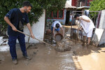 Locals try to move away water and mud from their homes following a storm at the village of Politika, on Evia island, northeast of Athens, on Sunday, Aug. 9, 2020. Five people have been found dead and dozens have been trapped in their homes and cars from a storm that has hit the island of Evia, in central Greece, police say. (AP Photo/Yorgos Karahalis)