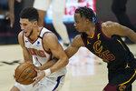 Phoenix Suns' Devin Booker, left, drives past Cleveland Cavaliers' Isaac Okoro in the first half of an NBA basketball game, Tuesday, May 4, 2021, in Cleveland. (AP Photo/Tony Dejak)