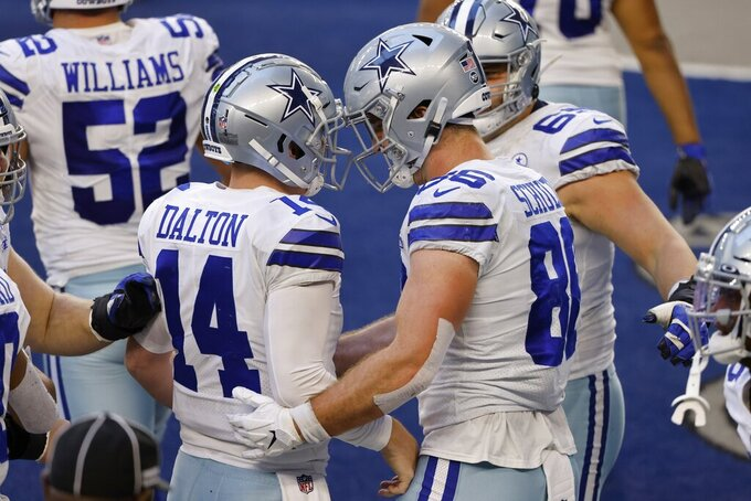 Dallas Cowboys' Andy Dalton (14) and Dalton Schultz (86) celebrate a touchdown catch by Schultz in the second half of an NFL football game against the San Francisco 49ers in Arlington, Texas, Sunday, Dec. 20, 2020. (AP Photo/Ron Jenkins)
