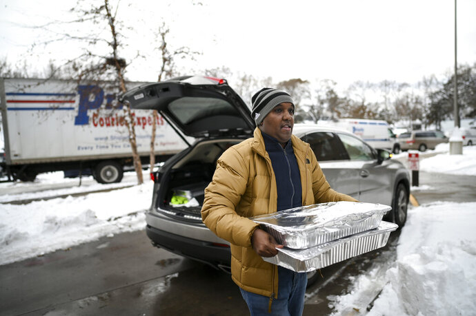 Abdirahman Kahin, owner of Afro Deli, donate food to residents of the Cedar Riverside, following a fire on the 14th floor of a public housing high-rise in Minneapolis on Wednesday, Nov. 27, 2019. Several people died and a few people were injured when the fire broke at the building in a heavily immigrant neighborhood of Minneapolis early Wednesday. (Aaron Lavinsky/Star Tribune via AP)