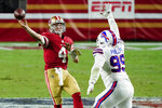 San Francisco 49ers quarterback Nick Mullens (4) throws over Buffalo Bills defensive tackle Harrison Phillips (99) during the second half of an NFL football game, Monday, Dec. 7, 2020, in Glendale, Ariz. The Bills won 34-24. (AP Photo/Rick Scuteri)