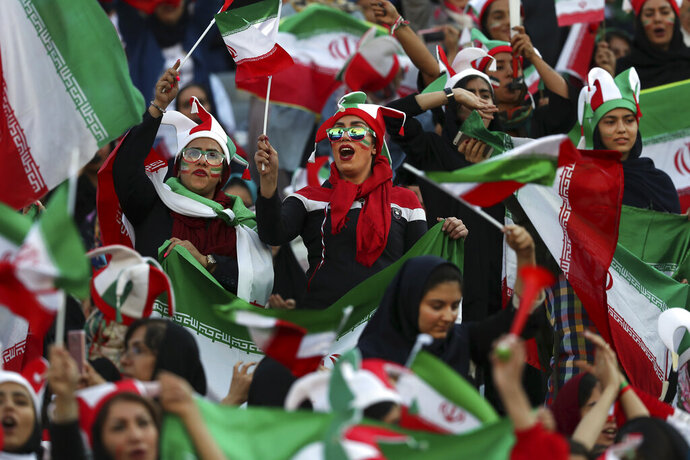 Iranian women cheer during a soccer match between their national team and Cambodia in the 2022 World Cup qualifier at the Azadi (Freedom) Stadium in Tehran, Iran, Thursday, Oct. 10, 2019. Iranian women were freely allowed into the stadium for the first time in decades. The decision follows the death of a young woman who set herself on fire after hearing she could face prison time for sneaking into an Iranian soccer match disguised as a man. (AP Photo/Vahid Salemi)