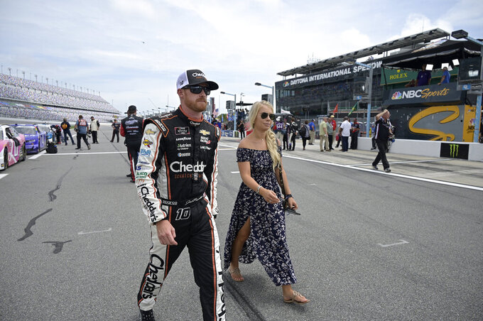 Driver Jeb Burton, left, and his wife Brandi walk to his vehicle on pit road before a NASCAR Xfinity Series auto race at Daytona International Speedway, Saturday, Aug. 28, 2021, in Daytona Beach, Fla. (AP Photo/Phelan M. Ebenhack)