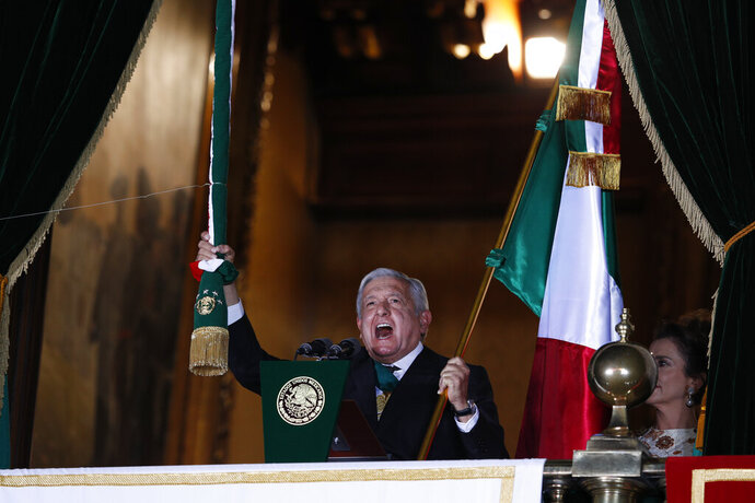 Mexican President Andres Manuel Lopez Obrador rings the bell as he gives the annual independence shout from the balcony of the National Palace to kick off subdued Independence Day celebrations amid the ongoing coronavirus pandemic, at the Zocalo in Mexico City, Tuesday, Sept. 15, 2020. Instead of the throngs of supporters who pack the Zocalo in a typical year, this Independence Day the president faced an empty plaza as he gave the traditional