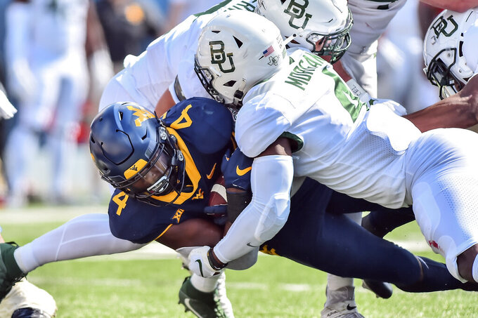 West Virginia running back Leddie Brown (4) is tackled by Baylor safety Christian Morgan (4)  during an NCAA college football game, Saturday, Oct. 3, 2020, in Morgantown, W.Va. (William Wotring/The Dominion-Post via AP)