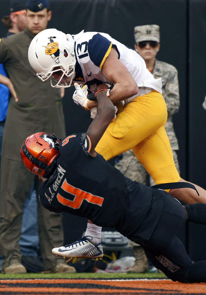 West Virginia wide receiver David Sills V struggles across the goal line while being tackled by Oklahoma State cornerback A.J. Green during the first half of an NCAA college football game in Stillwater, Okla., Saturday, Nov. 17, 2018. (AP Photo/Brody Schmidt)