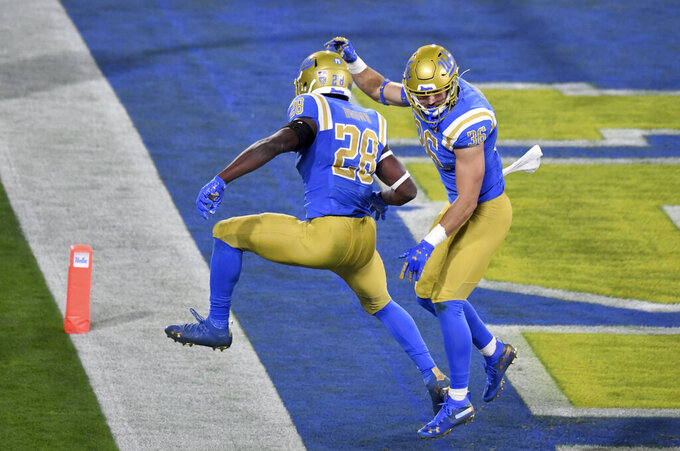 Wide receiver Ethan Fernea #36 celebrates with teammate unning back Brittain Brown #28 of the UCLA Bruins after catching a pass and runs for touchdown against the USC Trojans in the first half of a NCAA Football game at the Rose Bowl in Pasadena on Saturday, December 12, 2020. (Keith Birmingham/The Orange County Register via AP)