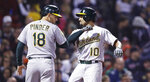 Oakland Athletics' Marcus Semien (10) is congratulated by Chad Pinder after his two-run home run off Boston Red Sox starting pitcher Chris Sale during the fifth inning of a baseball game at Fenway Park in Boston, Wednesday, May 16, 2018. (AP Photo/Charles Krupa)