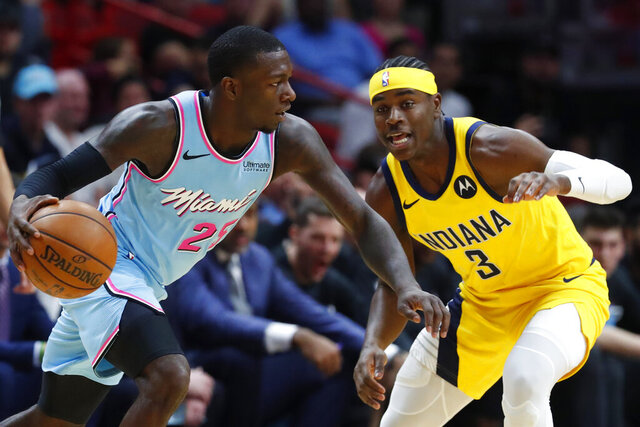 Miami Heat guard Kendrick Nunn (25) drives past Indiana Pacers guard Aaron Holiday (3) during the first half of an NBA basketball game Friday, Dec. 27, 2019, in Miami. (AP Photo/Wilfredo Lee)