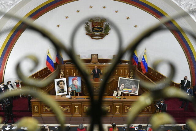 Seen through a balcony gate, the new president of Venezuela's National Assembly Jorge Rodriguez addresses newly sworn-in lawmakers as he is surrounded by photos of late Venezuelan President Hugo Chavez and independence hero Simon Bolivar at Congress in Caracas, Venezuela, Tuesday, Jan. 5, 2021. The ruling socialist party assumed the leadership of Venezuela's congress on Tuesday, the last institution in the country it didn't already control. (AP Photo/Matias Delacroix)