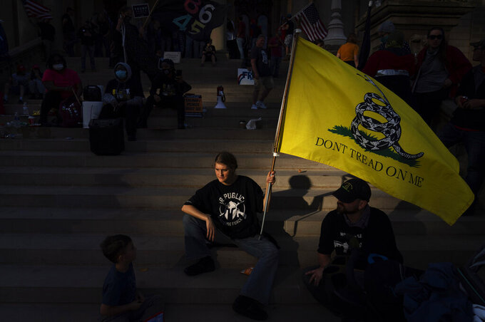 FILE - In this Nov. 8, 2020, file photo, a Donald Trump who would only give her first name, Dianna, sits on the steps of the State Capitol with her family as a protest against the presidential election results winds down in Lansing, Mich. While the state has swung back to Democrats since Trump's narrow 2016 win, choosing President Joe Biden by more than 150,000 votes, Michigan's Republican Party has taken a hard right turn. Its own Capitol in Lansing was the rallying point in April for armed Michigan Liberty Militia protesting pandemic restrictions, including some members who were later charged with plotting to kidnap Democratic Gov. Gretchen Whitmer. (AP Photo/David Goldman, File)