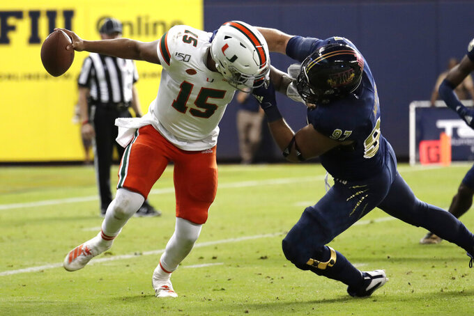 FIU defensive lineman Damon Moore, right, pulls on the face mask of Miami quarterback Jarren Williams (15) during the first half of an NCAA college football game, Saturday, Nov. 23, 2019, in Miami. (AP Photo/Lynne Sladky)
