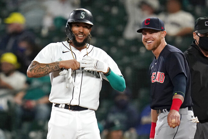 Seattle Mariners' J.P. Crawford, left, and Cleveland Indians first baseman Jake Bauers smile as they stand at first base after Crawford's single during the eighth inning of a baseball game Thursday, May 13, 2021, in Seattle. The hit was the first of the evening for the Mariners. (AP Photo/Elaine Thompson)