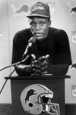 FILE - In this 1989, file photo, Detroit Lions first round draft pick Barry Sanders appears during a news conference after signing his first NFL contract at the Pontiac Silverdome in Pontiac, Mich. Jay Berwanger won the inaugural Heisman Trophy in 1935 and became the first player ever drafted by the NFL in a few months later. He chose to work at a rubber company and be a part-time coach for his alma mater, the University of Chicago, rather than try to make a living playing. More than five decades later, Oklahoma State Heisman Trophy winner Barry Sanders threatened to sue the NFL if it did not allow him to be drafted while he still had college eligibility. (AP Photo/John Stormzand, File)