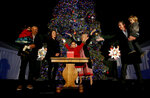Nayeli Lemus, 10, of Gilroy, center, raises his hands and celebrates after lighting the Capitol Christmas Tree with California first partner Jennifer Siebel Newsom, second from right and Gov. Gavin Newsom, right, holding his son, Dutch, in Sacramento, Calif., Thursday, Dec. 5, 2019. The more than 65-foot-tall white fir tree is decorated with hundreds of hand-crafted ornaments donated from the California Department of Developmental Services and 10,000 ultra-low-wattage LED lights. Also seen are Nayeli's family, father Angel Lemus, holding younger sister Naia, 2, left, and mother Rosalinda Lemus second from left.(AP Photo/Rich Pedroncelli)