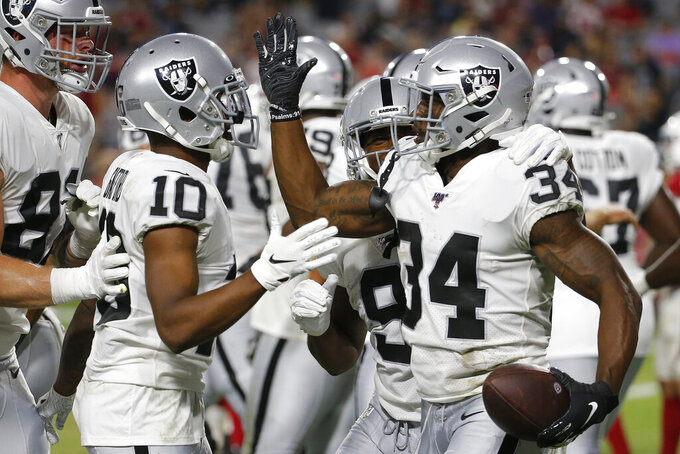 Oakland Raiders running back Mack Brown celebrates his touchdown against the Arizona Cardinals with wide receiver Rico Gafford (10) during the second half of an an NFL preseason football game, Thursday, Aug. 15, 2019, in Glendale, Ariz. (AP Photo/Rick Scuteri)