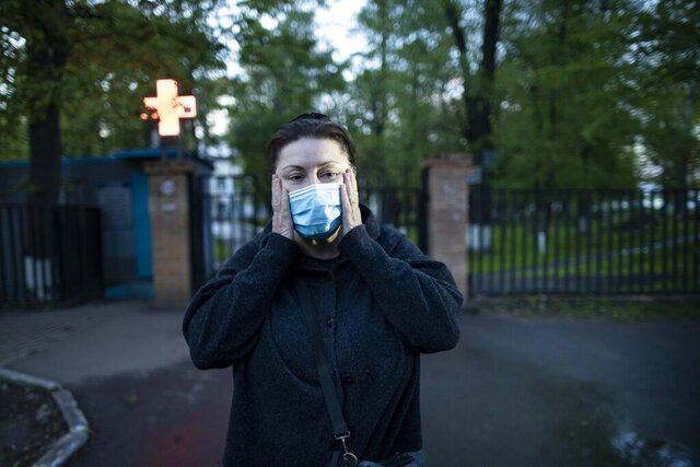 In this photo taken on Monday, May 18, 2020, Dr. Irina Vaskyanina adjusts a face mask to protect against coronavirus during her interview with the Associated Press in front of a hospital in Reutov, just outside Moscow, Russia. Vaskyanina headed a department handling blood transfusions at a hospital in Reutov, outside Moscow, and spent weeks fighting for better working conditions after 40 of her colleagues got infected with the virus and dozens quit. (AP Photo/Alexander Zemlianichenko)