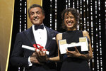 FILE - This May 25, 2019 file photo shows director Mati Diop, right, holding the grand prix Palme d'Or award for the film