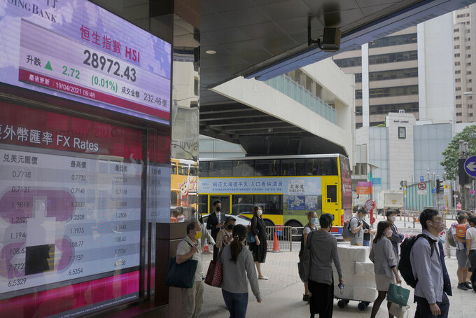 People walk past a bank's electronic board showing the Hong Kong share index at Hong Kong Stock Exchange in Hong Kong Monday, April 19, 2021. Asian shares were mixed Monday amid cautious optimism about a global rebound from the coronavirus pandemic. (AP Photo/Vincent Yu)