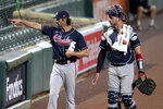 Atlanta Braves starting pitcher Cole Hamels, left, gestures to teammates sitting in the stands while walking with catcher Tyler Flowers to the dugout prior to a baseball game against the Baltimore Orioles, Wednesday, Sept. 16, 2020, in Baltimore. (AP Photo/Julio Cortez)